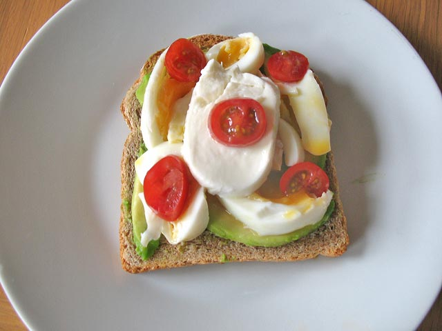 Boiled egg on toast with avocado, plum tomatoes and mozzarella cheese