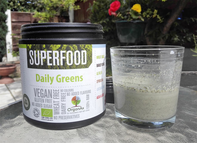 Superfood powder Daily Greens from OrganAx - in a small glass