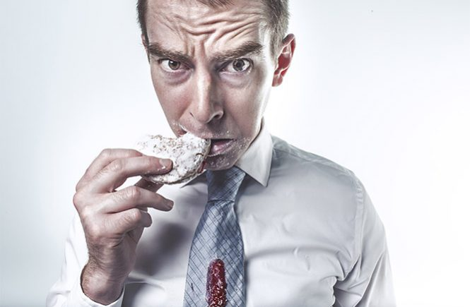 man snacking on doughnut